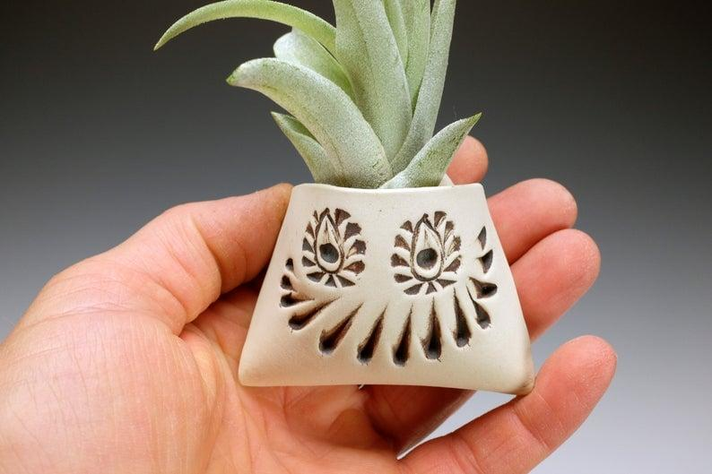 """<p>Give air plants a spooky holder to rest in with the <a href=""""https://www.popsugar.com/buy/Funny-Face-Air-Plant-Holder-492097?p_name=Funny%20Face%20Air%20Plant%20Holder&retailer=etsy.com&pid=492097&price=18&evar1=casa%3Aus&evar9=46619279&evar98=https%3A%2F%2Fwww.popsugar.com%2Fhome%2Fphoto-gallery%2F46619279%2Fimage%2F46636629%2FFunny-Face-Air-Plant-Holder&list1=shopping%2Challoween%2Cetsy%2Challoween%20decor%2Chome%20shopping&prop13=api&pdata=1"""" rel=""""nofollow"""" data-shoppable-link=""""1"""" target=""""_blank"""" class=""""ga-track"""" data-ga-category=""""Related"""" data-ga-label=""""https://www.etsy.com/listing/723079983/funny-face-air-plant-holder-wall-pocket"""" data-ga-action=""""In-Line Links"""">Funny Face Air Plant Holder</a> ($18).</p>"""