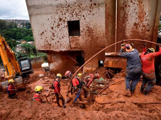 Firefighters search for missing persons using a hydraulic dismantling technique, which uses water to disperse mud, in Belo Horizonte (AFP via Getty Images)