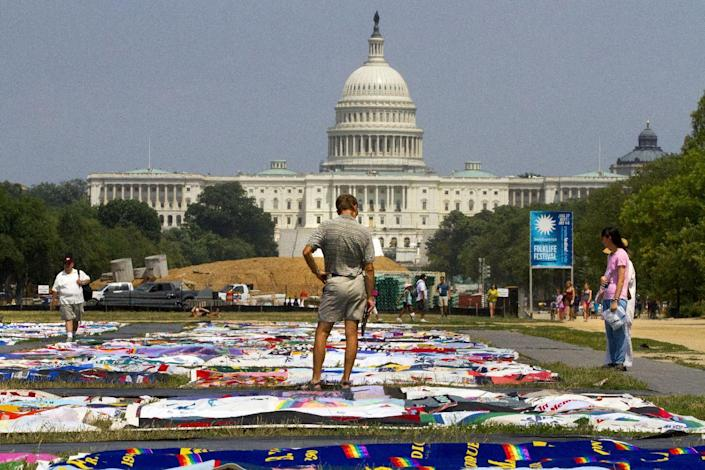 People visit the AIDS Memorial Quilt on display as part of the Smithsonian Folklife Festival on the National Mall in Washington, Thursday, July 5, 2012. An AIDS-free generation: It seems an audacious goal, considering how the HIV epidemic still is raging around the world. Yet more than 20,000 international HIV researchers and activists will gather in the nation's capital later this month with a sense of optimism not seen in many years _ hope that it finally may be possible to stem the spread of the AIDS virus. (AP Photo/Jacquelyn Martin)