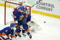 New York Islanders' Scott Mayfield (24) defends against Washington Capitals center Nicklas Backstrom (19) as Islanders goaltender Semyon Varlamov (40) makes a save during the second period of an NHL hockey game Thursday, April 22, 2021, in Uniondale, N.Y. (AP Photo/Kathy Willens)