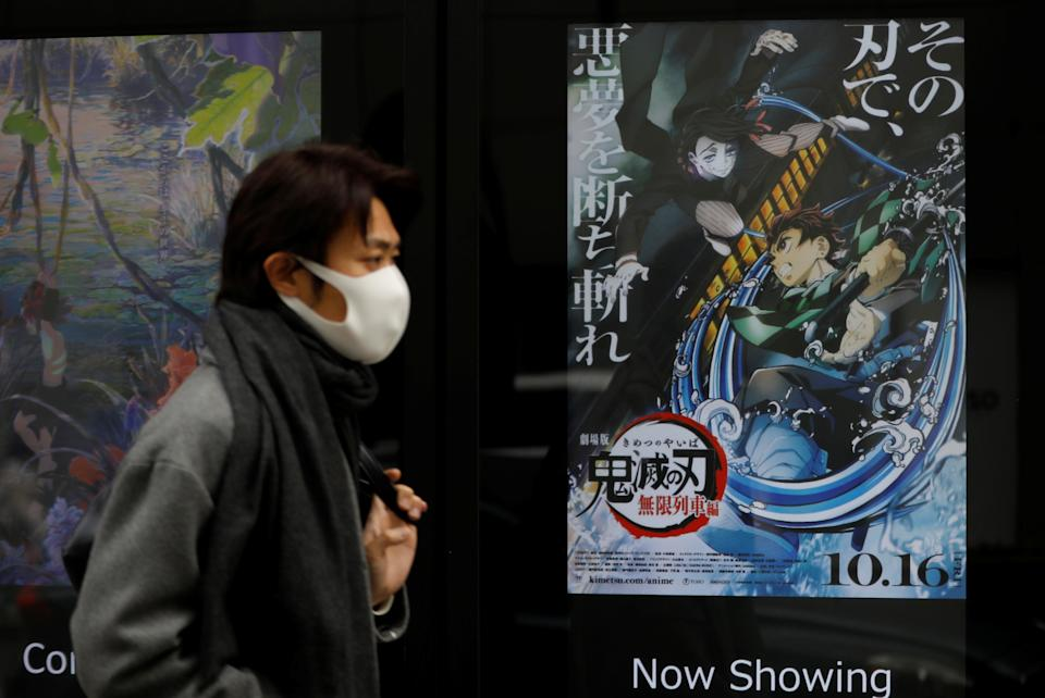 """A man wearing a protective mask amid the coronavirus disease (COVID-19) outbreak walks past a poster for an animated movie """"Demon slayer"""" in front of a movie theatre in Tokyo, Japan, December 13, 2020. Picture taken December 13, 2020. REUTERS/Kim Kyung-Hoon"""