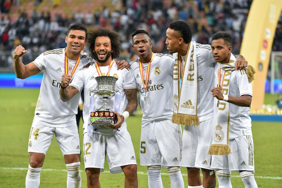 (L To R) Real Madrid's Brazilian players Casemiro, Marcelo, Vinicius Junior, Eder Militao and Rodrygo pose with the trophy after winning the Spanish Super Cup final between Real Madrid and Atletico Madrid on January 12, 2020, at the King Abdullah Sports City in the Saudi Arabian port city of Jeddah. (Photo by FAYEZ NURELDINE / AFP) (Photo by FAYEZ NURELDINE/AFP via Getty Images)