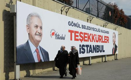 """People walk past by AK Party billboards with pictures of Turkish President Tayyip Erdogan and mayoral candidate Binali Yildirim in Istanbul, Turkey, April 1, 2019. The billboards read: """" Thank you Istanbul """".  REUTERS/Huseyin Aldemir/File Photo"""