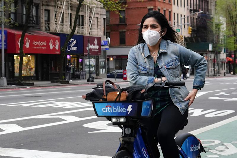 NEW YORK, NEW YORK - APRIL 30: A woman rides a citibike while wearing a protective mask during the coronavirus pandemic on April 30, 2020 in New York City. COVID-19 has spread to most countries around the world, claiming over 230,000 lives with infections over 3.2 million people. (Photo by Cindy Ord/Getty Images)