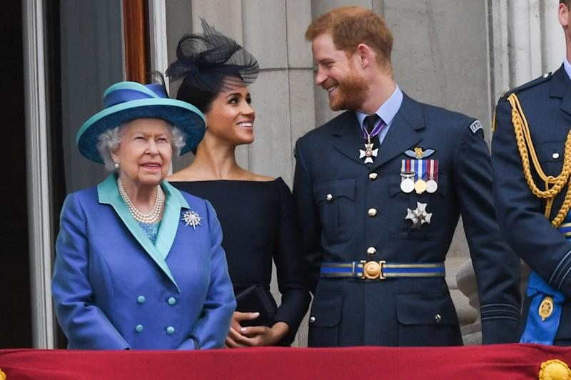 LONDON, UNITED KINGDOM - JULY 1O: Queen Elizabeth ll, Meghan, Duchess of Sussex and Prince Harry, Duke of Sussex stand on the balcony of Buckingham Palace to view a flypast to mark the centenary of the Royal Air Force (RAF) on July 10, 2018 in London, England. (Photo by Anwar Hussein/WireImage)