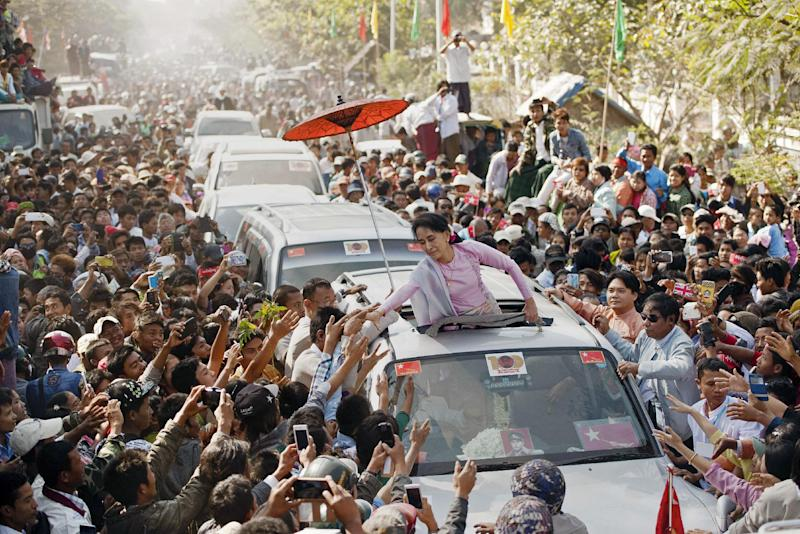 Myanmar opposition leader Aung San Suu Kyi (C) greets supporters at celebrations to mark the 100th birthday of the country's independence hero, her father Aung San, in the remote central Myanmar town of Natmauk on February 13, 2015 (AFP Photo/Ye Aung Thu)