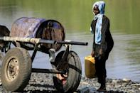 A woman carries water next to a donkey cart in Fashaqa, where rural life has been upended by regional tensions