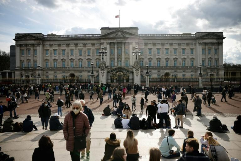 People gather outside Buckingham Palace where the Union Flag flies at half-mast
