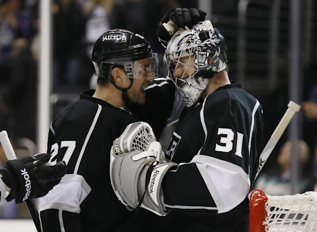 Los Angeles Kings' goaltender Martin Jones (31) celebrates a shutout with teammate Alec Martinez, left, after an NHL hockey game against the Edmonton Oilers in Los Angeles, Tuesday, Dec. 17, 2013. The Kings won 3-0. (AP Photo/Danny Moloshok)