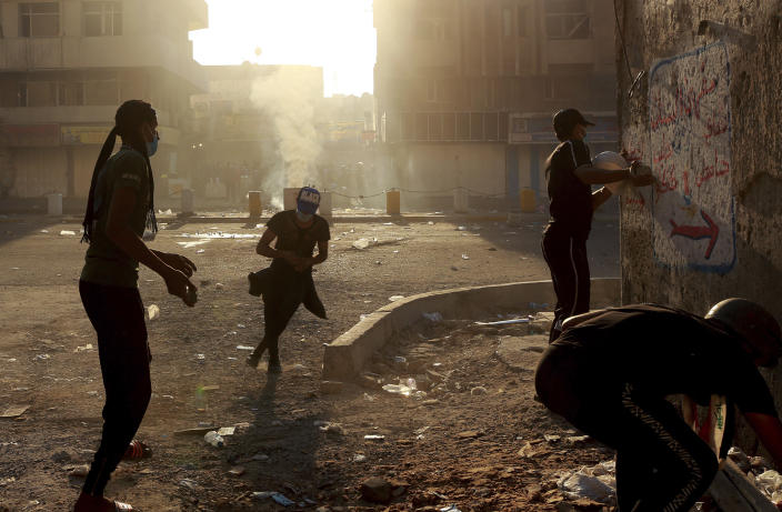 Iraqi riot police fire tear gas to disperse anti-government protesters during ongoing protests in central Baghdad, Iraq, Saturday, Nov. 9, 2019. The protests intensified Saturday afternoon as demonstrators tried to reach the three bridges, hours after being pushed back under clouds of tear gas from the Sinak bridge to the nearby Khilani square. (AP Photo/Hadi Mizban)