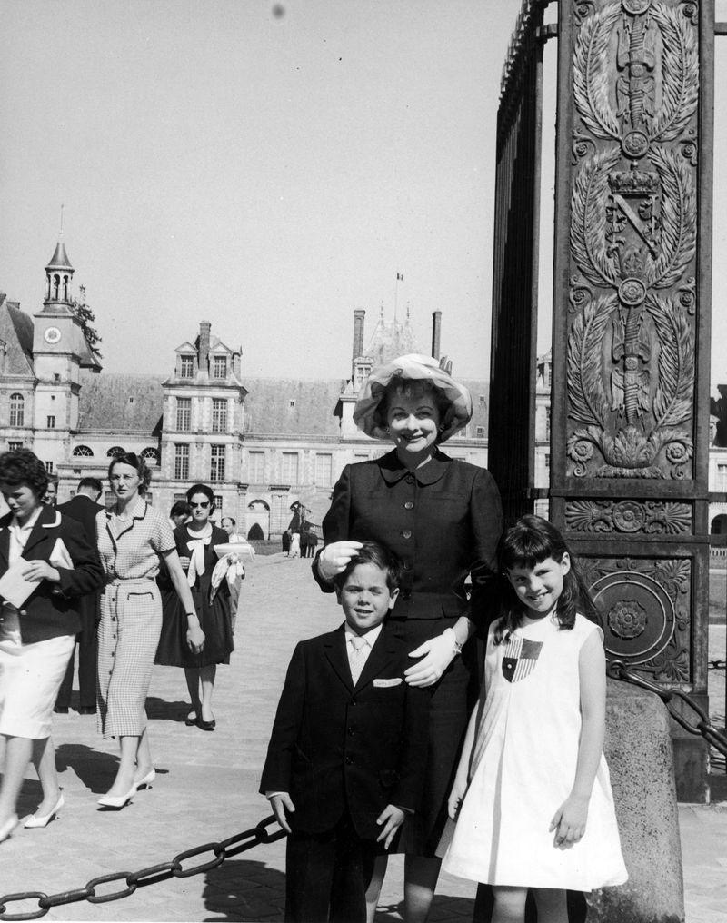 <p>Lucille Ball and her children smile outside of the Chateau de Fontainebleau near Paris. The TV star took her children sightseeing on a European vacation in 1959.</p>