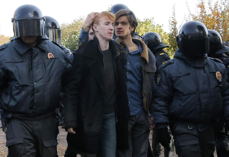 Riot police detain gay rights activists after a scuffle with anti-gay protesters during an LGBT rally in St. Petersburg, Russia, Saturday, Oct. 12, 2013. A gay rights rally in St. Petersburg has ended in scuffles after several dozen protesters were confronted by about 200 conservative and religious activists. The police standing nearby waited until clashes broke out between the two groups before intervening. According to Russian news agencies, the police detained 67 people from both sides. (AP Photo/Dmitry Lovetsky)