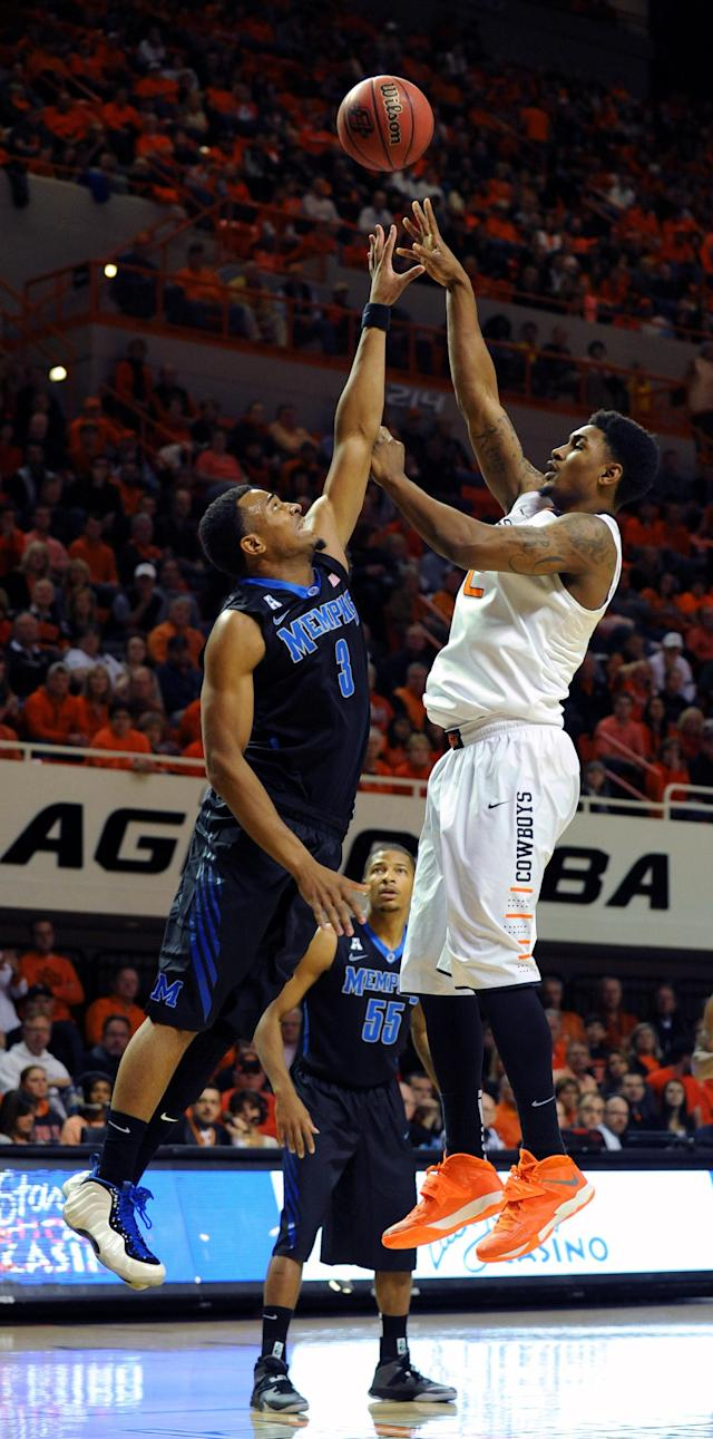 Oklahoma State wing Le'Bryan Nash, right, takes a shot over Memphis guard Chris Crawford during the first half of an NCAA college basketball game in Stillwater, Okla., Tuesday, Nov. 19, 2013. (AP Photo/Brody Schmidt)