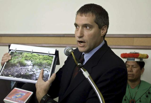 Attorney Steven Donziger shows pictures of a pool of oil which seeped out from an oil waste pit left behind by Texaco at an oil pump site in the Amazon jungle, in Quito, in this October 30, 2003 file photo. REUTERS/Franklin Jacome/Files