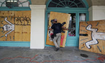 In preparation of Hurricane Ida, a workers attach protective plywood to windows and doors of a business in the French Quarter in New Orleans, Saturday, Aug. 28, 2021. (AP Photo/Eric Gay)