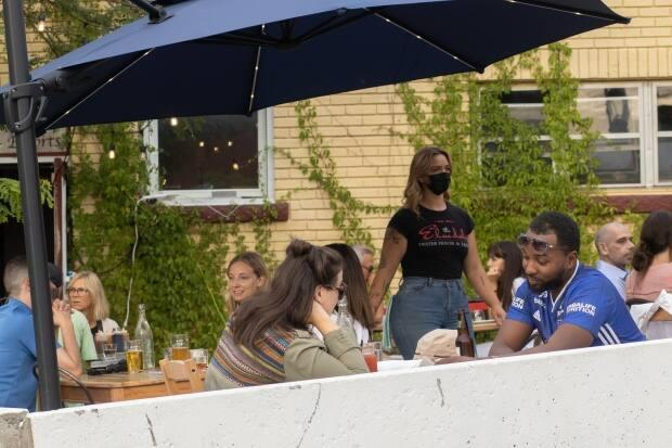 People dine on the patio of the Elmdale Tavern in Ottawa's Hintonburg neighbourhood last Friday. A COVID-19 vaccine will not be required to dine on patios in Ontario, but will be required for indoor dining. (Trevor Pritchard/CBC - image credit)