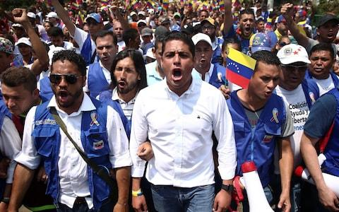 Venezuela's opposition lawmaker Jose Manuel Olivares and supporters march toward the Simon Bolivars bridge on the outskirts of Cucuta - Credit: Reuters
