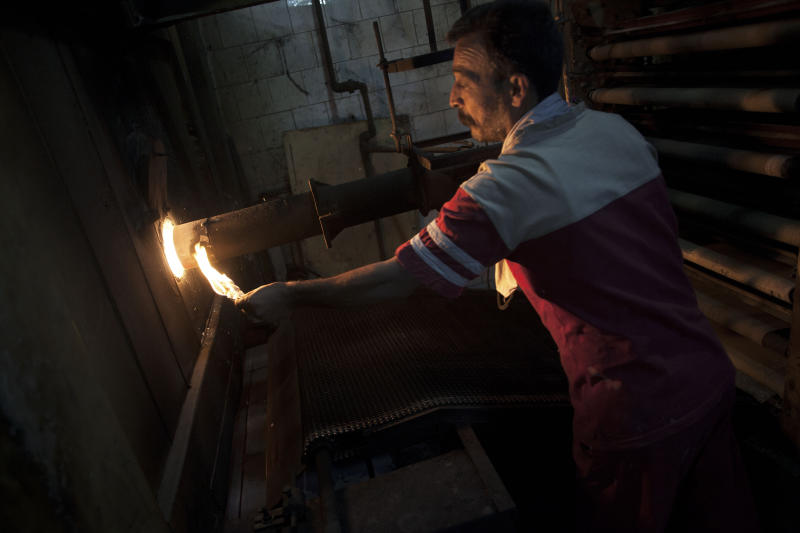In this Sunday, Oct. 14, 2012 photo, a Syrian man turns on the oven at his bakery shop on the outskirts of Aleppo, Syria. The Aleppo rebellion started off in the rural areas of Aleppo province, not in the city as was the case in most other parts of Syria. Until this day, all of Aleppo's rebel-held areas are poor, while the city's affluent parts remain under government control with life there reportedly continuing much as it had before. Regime forces punish the city daily with artillery and airstrikes. Civilians are killed and wounded while standing on breadlines, walking the streets or watching television at home. (AP Photo/ Manu Brabo)