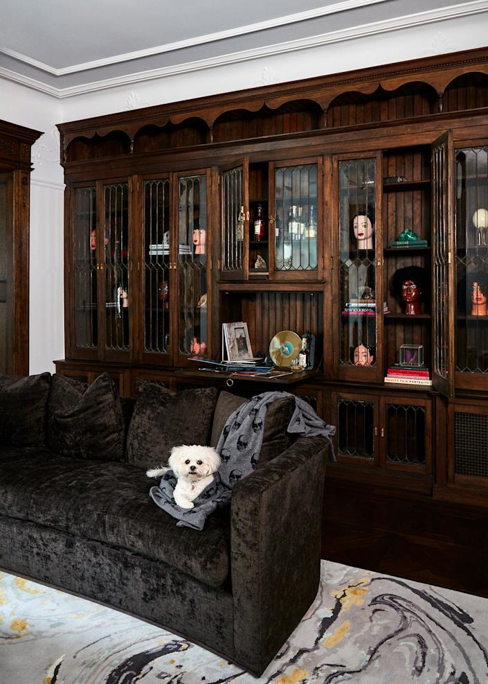 "<div class=""caption""> Bisou, a Bichon–Shih Tzu mix that Gillian calls ""the queen of the castle,"" sits regally on the library's curved sofa (a Gesine model from <a href=""https://www.thebrightgroup.com"" rel=""nofollow noopener"" target=""_blank"" data-ylk=""slk:The Bright Group"" class=""link rapid-noclick-resp"">The Bright Group</a>). Restoring the bookshelf, which features a series of head sculptures by Ghanaian craftsman <a href=""https://www.thefutureperfect.com/made-by/designer/jacob-tetteh-ashong-paa-joe/"" rel=""nofollow noopener"" target=""_blank"" data-ylk=""slk:Jacob-Tetteh Ashong"" class=""link rapid-noclick-resp"">Jacob-Tetteh Ashong</a> (son of artist Paa Joe), was a laborious process that involved sourcing pieces of glass and bits of hardware from neighbors. </div>"