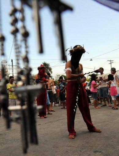 A penitent self-flagellates on the eve of the Good Friday reenactments of the crucifixion of Jesus Christ in front of a church in San Fernando City, Pampanga province, north of Manila, on April 5