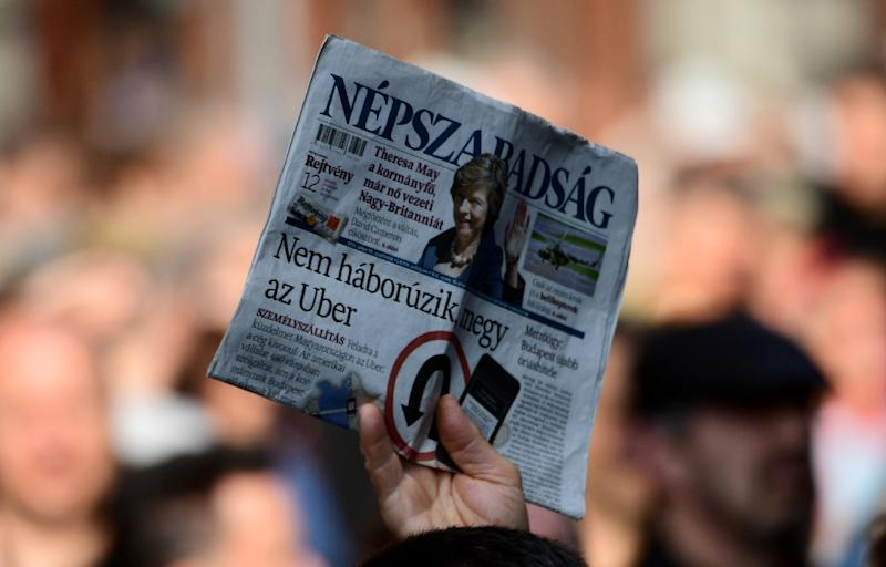 A person holds a copy of Nepszabadsag daily during a protest by journalists of Hungary's biggest opposition newspaper Nepszabadsag and their supporters in Budapest on October 16, 2016 (AFP Photo/Attila Kisbenedek)