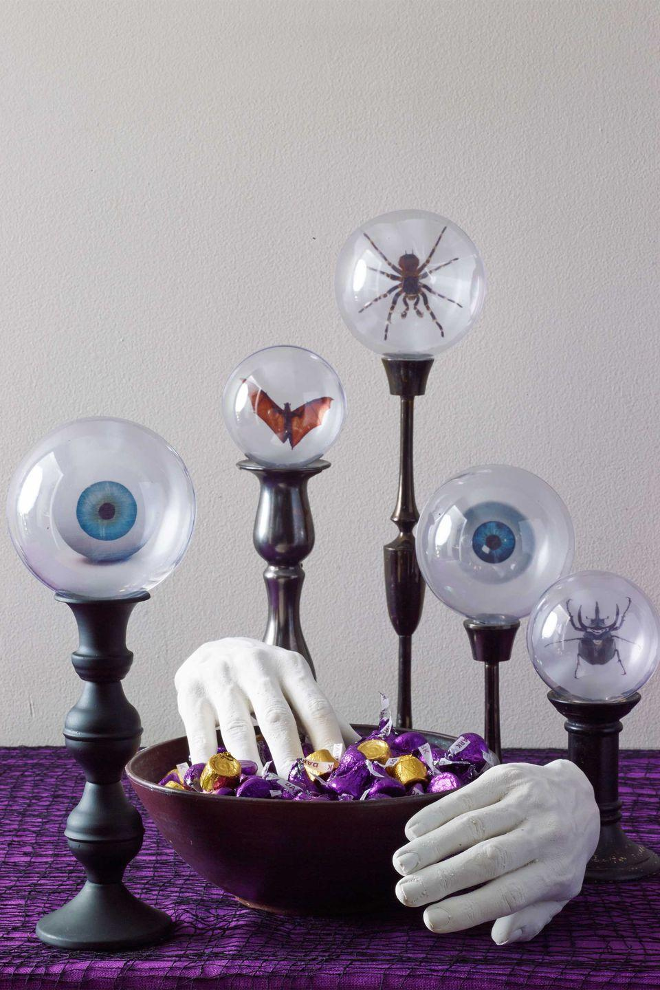 """<p>To create these floating creepy-crawlies, print free images from <em><a href=""""http://www.freepik.com/"""" rel=""""nofollow noopener"""" target=""""_blank"""" data-ylk=""""slk:freepik.com"""" class=""""link rapid-noclick-resp"""">freepik.com</a> </em>onto paper vellum. Separate the halves of plastic ornaments, then lay one half flat-side down over the image, trace and cut out. Place the image cutout between the ornament halves, snap together and balance upside down on candlesticks. These grabby fingers look lifelike because they're made using molds of your very own hands. </p><p><strong>What You'll Need</strong>: <a href=""""https://www.amazon.com/Seekingtag-Clear-Plastic-Fillable-Ornaments/dp/B017VXXXHU/ref=sr_1_3?dchild=1&keywords=plastic+snappable+ornaments&qid=1595000703&sr=8-3&tag=syn-yahoo-20&ascsubtag=%5Bartid%7C10070.g.1279%5Bsrc%7Cyahoo-us"""" rel=""""nofollow noopener"""" target=""""_blank"""" data-ylk=""""slk:Plastic ornaments"""" class=""""link rapid-noclick-resp"""">Plastic ornaments </a>($10, Amazon); <a href=""""https://www.amazon.com/Perfect-Craft-Gestures-Molding-Casting/dp/B004PJAOXA/ref=sr_1_14?dchild=1&keywords=hand+mold+kit&qid=1595000746&sr=8-14&tag=syn-yahoo-20&ascsubtag=%5Bartid%7C10070.g.1279%5Bsrc%7Cyahoo-us"""" rel=""""nofollow noopener"""" target=""""_blank"""" data-ylk=""""slk:cast molding kit"""" class=""""link rapid-noclick-resp"""">cast molding kit </a>($30, Amazon); <a href=""""https://www.amazon.com/SUNFACE-Portavelas-7-9-3-1-11-8/dp/B07N657QYB/ref=sr_1_5?dchild=1&keywords=black+candle+holders&qid=1595000819&sr=8-5&tag=syn-yahoo-20&ascsubtag=%5Bartid%7C10070.g.1279%5Bsrc%7Cyahoo-us"""" rel=""""nofollow noopener"""" target=""""_blank"""" data-ylk=""""slk:candle sticks"""" class=""""link rapid-noclick-resp"""">candle sticks</a> ($29, Amazon)</p>"""