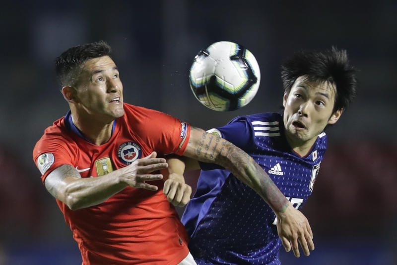 Chile's Charles Aranguiz, left, and Japan's Shoya Nakajima vie for the ball during a Copa America Group C soccer match at the Morumbi stadium in Sao Paulo, Brazil, Monday, June 17, 2019. (AP Photo/Andre Penner)