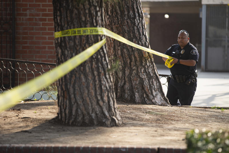 Police set a perimeter outside the Park Avenue Elementary school in Cudahy, Calif., Tuesday, Jan. 14, 2020. Fire officials say fuel apparently dumped by the aircraft returning to LAX fell onto the elementary school playground.  (AP Photo/Damian Dovarganes)