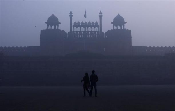 A couple walks in front of the historic Red Fort amid dense fog on a cold winter morning in the old quarters of Delhi January 3, 2012.
