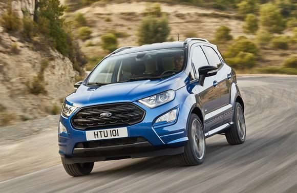 A blue 2018 Ford EcoSport, a small SUV, with UK license plate, on a country road.