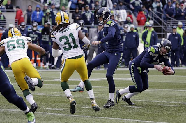 Seattle Seahawks' Jon Ryan (9) prepares to throw a touchdown pass on a fake field goal attempt during the second half of the NFL football NFC Championship game against the Green Bay Packers Sunday, Jan. 18, 2015, in Seattle. (AP Photo/David J. Phillip)