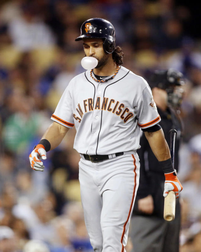 San Francisco Giants' Angel Pagan blows a bubble and walks back to the dugout after striking out looking against the Los Angeles Dodgers during the third inning of a baseball game, Friday, May 9, 2014, in Los Angeles. (AP Photo/Danny Moloshok)