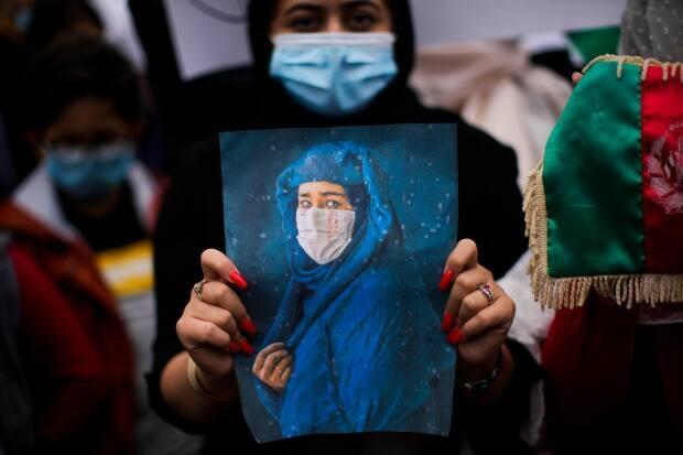 A woman holds a photograph during a protest to raise awareness about the situation in Afghanistan outside European Union headquarters in Brussels, on Aug. 18, 2021.  (Francisco Seco/The Associated Press - image credit)