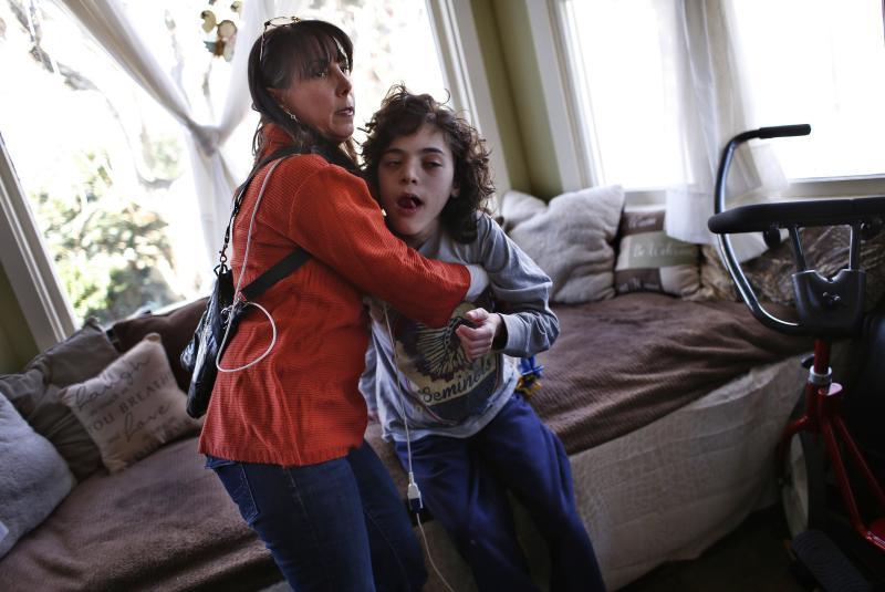 Missy Miller holds her epileptic son Oliver (R) in their home at Atlantic Beach, New York January 7, 2014. Oliver suffered a brain stem injury in utero and now, at 14, has hundreds of seizures a day. For months, his family has pinned their hopes on a strain of marijuana developed in Colorado that has helped children with similar conditions. But under an executive order by Governor Andrew Cuomo on Wednesday making New York the 21st state to allow medical marijuana, it will remain illegal to grow marijuana or to import specialized plants from other states. Patients will have little say in the marijuana they are prescribed and people like Oliver - who could benefit from a specialized strain known as Charlotte's Web that is high in the compound cannabidiol, or CBD, - would be cut out entirely. Picture taken January 7, 2014. REUTERS/Mike Segar (UNITED STATES - Tags: HEALTH POLITICS)