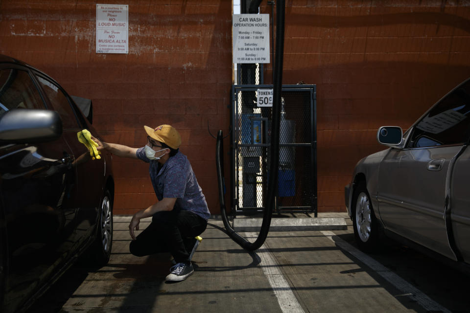 Jesus Ramirez wears a face mask while washing his car during the coronavirus pandemic in the Vermont Square neighborhood of Los Angeles, Thursday, May 21, 2020. While most of California took another step forward to partly reopen in time for Memorial Day weekend, Los Angeles County didn't join the party because the number of coronavirus cases has grown at a pace that leaves it unable to meet even the new, relaxed state standards for allowing additional businesses and recreational activities. (AP Photo/Jae C. Hong)