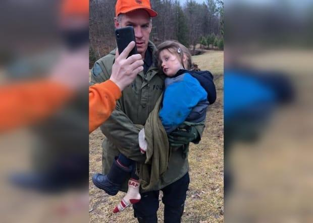 Const. Scott McNames carries Jude Leyton moments after locating the three-year-old alive and well in a forest north of Kingston, Ont., after a search effort that lasted approximately 75 hours. (911 Blue on Blue/Facebook - image credit)