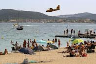 People on the beach watch a Canadair aircraft fill its tank from the sea in the bay of Saint-Tropez.
