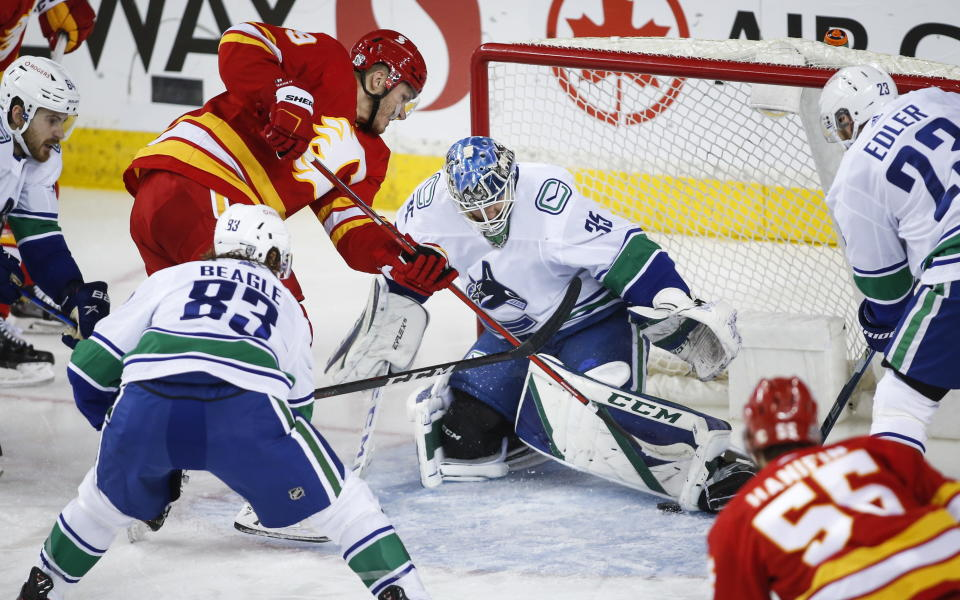 Vancouver Canucks goalie Thatcher Demko, right, gets his pad on a shot from Calgary Flames' Matthew Tkachuk during second-period NHL hockey game action in Calgary, Alberta, Monday, Jan. 18, 2021. (Jeff McIntosh/The Canadian Press via AP)
