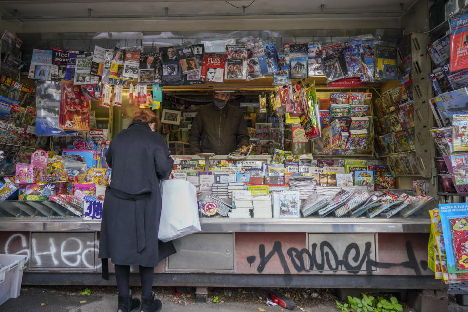 Armando Alviti, 71, stands inside his newspaper kiosk as he serves a client, in Rome, Friday, Dec. 4, 2020. In Italy, which has the world's second-oldest population, many people in their 70s and older have kept working through the COVID-19 pandemic. From neighborhood newsstand dealers to farmers bring crops to market, they are defying stereotypic labels that depict the old as a monolithic category that's fragile and in need of protection. (AP Photo/Andrew Medichini)