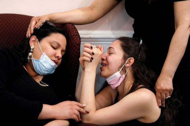 PHOTO: Jessica Holguin, 25, comforts her younger sister Natalie Holguin at the viewing service of their father Jose Holguin, who died of complications related to the coronavirus disease, in the Harlem neighborhood of New York, May 16, 2020. (Andrew Kelly/Reuters)