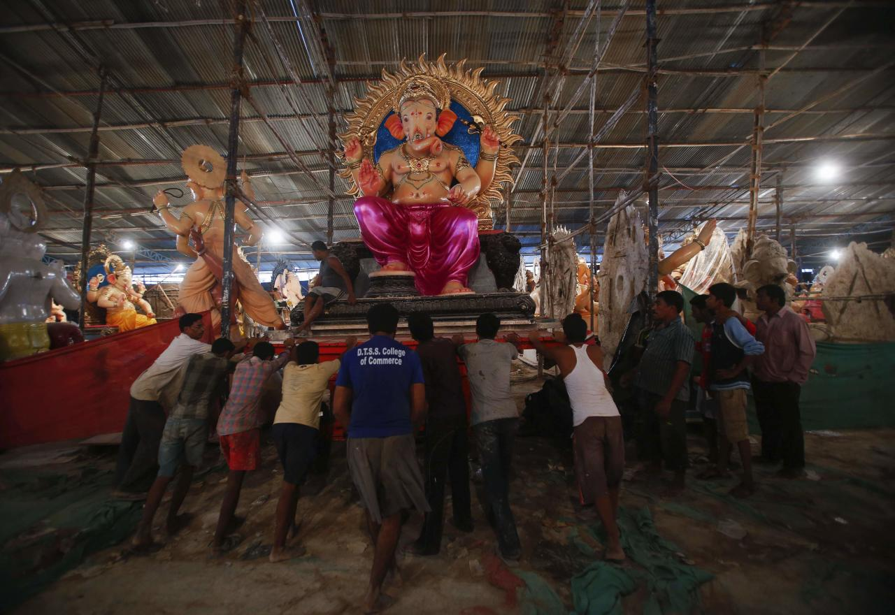"""Workers push a trolley with an idol of Hindu elephant god Ganesh, the deity of prosperity, as it is transported from a workshop to a place of worship in Mumbai September 3, 2013. The idols will be paraded through the streets in a procession during the Ganesh Chaturthi festival, accompanied by dancing and singing. They will then be immersed in a river or the sea symbolizing a ritual send-off of Ganesh's journey towards his abode in """"Kailash"""", while taking away with him the misfortunes of all mankind. The festival will be celebrated on September 9. REUTERS/Danish Siddiqui (INDIA - Tags: SOCIETY RELIGION)"""