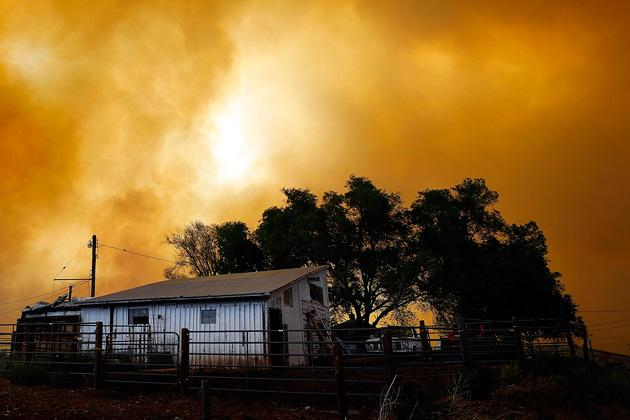 Smoke fills the air over a small barn turning the sky orange as the High Park Fire burns near Laporte, Colorado June 10, 2012. The fire started on Saturday and was estimated at more than 14,000 acres on Sunday morning. At least 18 structures were lost or damaged due to the fire with more threatened and officials are searching for one person believed to be missing. The cause of the fire is unknown and it remains at zero percent containment. REUTERS/Marc Piscotty