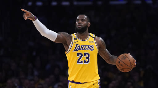 FILE - In this March 6, 2020, file photo, Los Angeles Lakers forward LeBron James gestures to teammates during the second half of an NBA basketball game against the Milwaukee Bucks in Los Angeles. James was announced Saturday, Dec. 26, as the winner of The Associated Press Male Athlete of the Year award for a record-tying fourth time.(AP Photo/Mark J. Terrill, File)