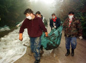 FILE - In this Oct. 9, 1996. file photo, Bosnian workmen carry the body of a Muslim allegedly killed by Bosnian Serbs in 1992, dug out from a cave together with seventy others, in Laniste, 170 kilometers (105 miles) northwest of Sarajevo, Bosnia. While it brought an end to the fighting, the Dayton peace agreement baked in the ethnic divisions, establishing a complicated and fragmented state structure with two semi-autonomous entities, Serb-run Republika Srpska and a Federation shared by Bosniak and Croats, linked by weak joint institutions. (AP Photo/Darko Bandic, File)