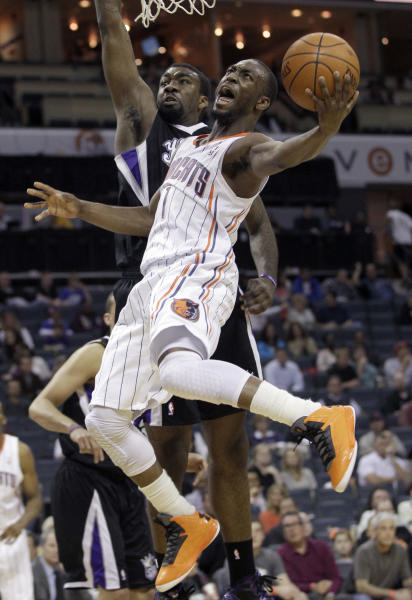Charlotte Bobcats' Kemba Walker, front, drives past Sacramento Kings' Donte Greene during the first half of an NBA basketball game in Charlotte, N.C., Sunday, April 22, 2012. (AP Photo/Chuck Burton)