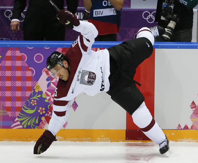 Latvia forward Martins Karsums trips in the first period of a men's ice hockey game against Switzerlands at the 2014 Winter Olympics, Tuesday, Feb. 18, 2014, in Sochi, Russia. (AP Photo/Julio Cortez)