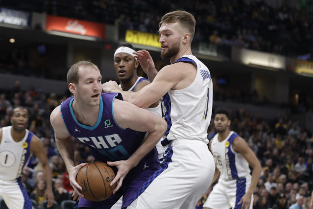 Charlotte Hornets' Cody Zeller (40) makes a pass against Indiana Pacers' Domantas Sabonis (11) during the first half of an NBA basketball game, Sunday, Dec. 15, 2019, in Indianapolis. (AP Photo/Darron Cummings)