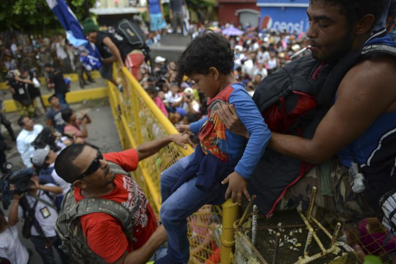 A child is passed over a border fence between Guatemala and Mexico on Friday. (ASSOCIATED PRESS)