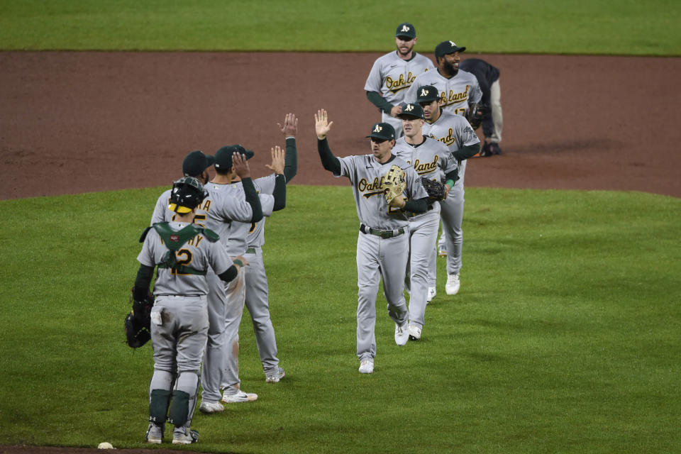 Oakland Athletics' Ramon Laureano, center facing camera, and the rest of the team celebrate a 7-2 win over the Baltimore Orioles in a baseball game Saturday, April 24, 2021, in Baltimore. (AP Photo/Gail Burton)