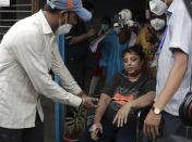 Health workers shift a patient after a fire in Vijay Vallabh COVID-19 hospital at Virar, near Mumbai, India, Friday, April 23, 2021. A fire killed 13 COVID-19 patients in a hospital in western India early Friday as an extreme surge in coronavirus infections leaves the nation short of medical care and oxygen. (AP Photo/Rajanish Kakade)